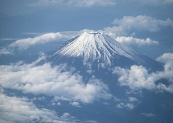 This picture shows Mount Fuji, Japan's highest mountain at 3,776 meters (12,388 feet), seen from the window of a passenger aircraft en route to Kagoshima on May 14, 2021. (Photo by Charly TRIBALLEAU / AFP)